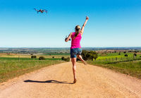 Woman leaping for joy along dirt road flying a drone