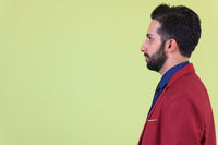 Closeup profile view of young bearded Persian businessman in suit