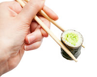 chopsticks hold kappa roll with cucumber close up