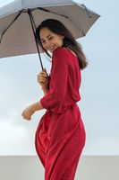 Portrait of beautiful young woman with umbrella in city at rainy day