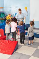 Sportlehrerin verteilt Bälle an Kinder