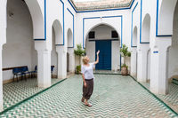Woman admiring traditional moroccan architecture in one of the palaces in medina of Marrakesh, Morocco.