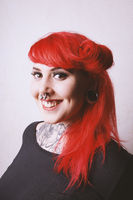 pierced and tattooed young woman with toothy smile