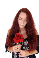 Woman with red hair looking down on her red rose
