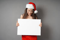 female santa looking down at blank sign with copy space
