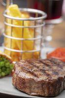 Nahaufnahme vom gegrillten Steak mit Pommes frites