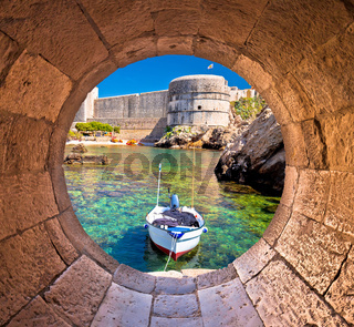 Dubrovnik small harbor under city walls view through stone carved window