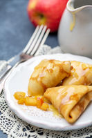 Homemade crepes with apples and caramel sauce.