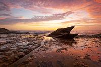 Sunrise on coastal beach rock shelf with reflections low tide