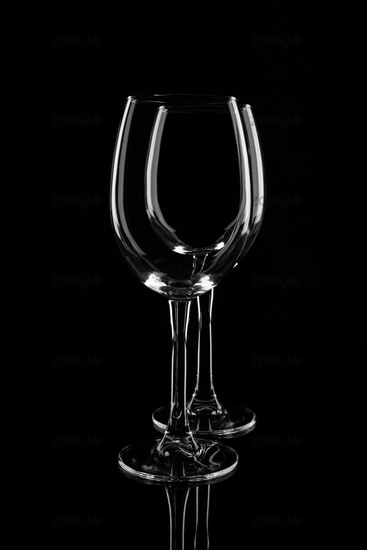 Two empty transparent wine glasses, isolated on black background