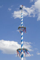 Bavarian maypole in front of white blue cloud sky