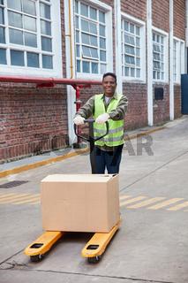 Arbeiter transportiert Paket auf dem Hubwagen