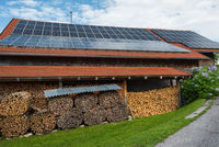 Stacked fire wood in barn with photovoltaic panels on roof