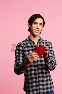 Sweet guy in checkered shirt offering red heart, Valentine's day