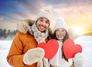 happy couple with red hearts over winter nature