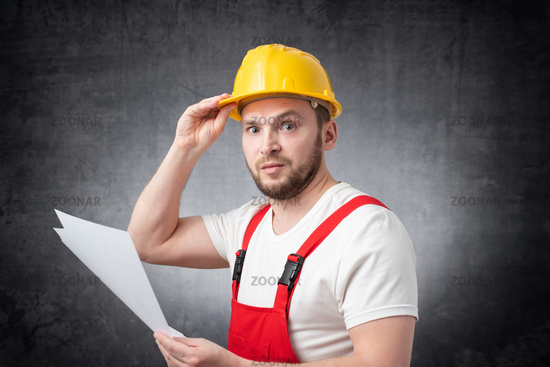 Confused construction worker holding papers