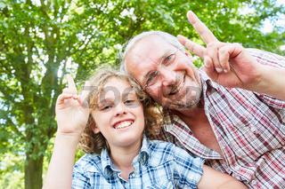 Großvater und Enkel machen das Siegeszeichen