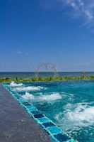 An infinity pool with jacuzzi at a beach resort