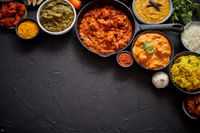 Composition of Indian cuisine in ceramic bowls on black stone table