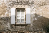 Old window with wooden white painted open shutters