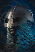 Soldier Viking helmet with chain mail of iron on red shield of wood and golden triskel