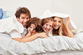 Familie mit zwei Kindern unter einer Bettdecke