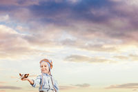 Little boy pilot in the sunset sky
