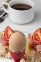 Nahaufnahme von einem gekochten Ei mit Kaffee