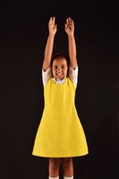 Little girl in school uniform  doing  PT exercise in front of camera on black backdrop, Pune, Maharashtra