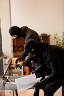 Zwei Einbrecher durchsuchen Schubladen