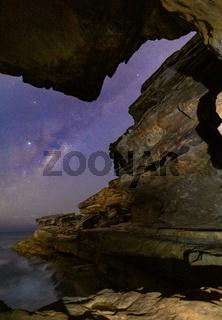Milky Way viewed through a narrow crack in coastal  rock formation