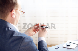 Middle age Man Pierce his fingertip before doing blood test with personal glucometer. Place for text