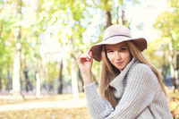 Portrait of a beautiful young blond woman with shiny straight hair in a brown hat in the park
