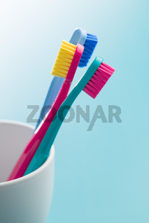Colorful toothbrushes in cup.