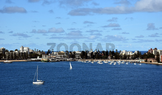 Manly buildings skyline from Dobroyd Head lookout on a sunny day in summer. Many yachts in North Harbour.