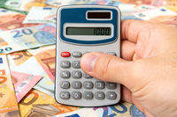Businessman with calculator counts money