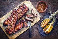 Barbecue spare ribs St Louis cut with hot honey chili marinade and pineapple as top view on a rustic cutting board with copy space