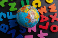 Globe model on colorful letters on a black background