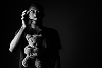 Sad depressed young African man with teddy bear and love sign text in black and white