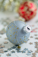 Silver Christmas ball with gold ornament.