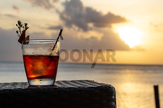 An iced summer cocktail isolated in front of a sunset over the sea