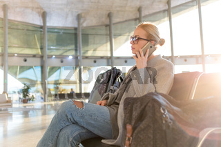 Female traveler talking on her cell phone while waiting to board a plane at departure gates at airport terminal.