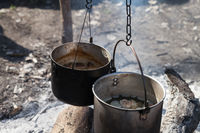 Cooking in two sooty old cauldrons on campfire