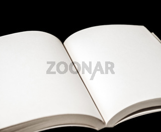 Open blank book on black background