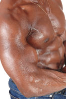 The close up sweaty torso of a black man bodybuilder