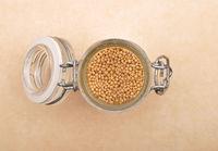 Senfkörner in Glas auf braunem Hintergrund - Mustard seeds in glass on brown background