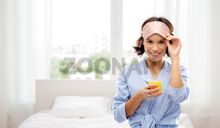 woman in pajama and sleeping mask with juice