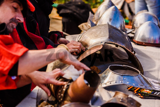 Valencia, Spain - January 27, 2019: Artisans disguised as medieval era burnishing dirty armor to clean them.