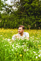 Male student is sitting in the tall grass