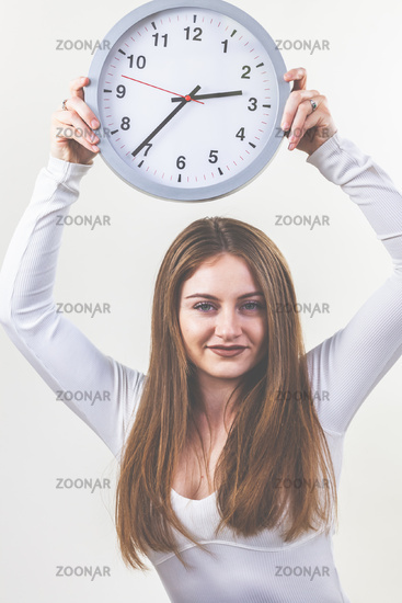 Woman, white shirt and jeans, brunette, long hair, holding a clock in her hands. Appointment.